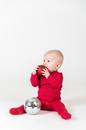 6 9 months: Sitting smiling baby in red with party ball Stock Photo