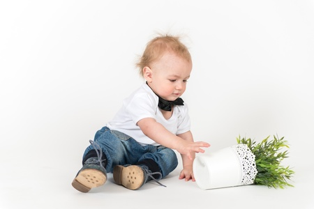6 9 months: Little boy sits with the plant