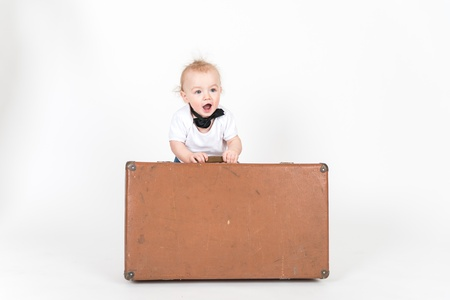 6 9 months: Little boy with the suitcase on the white background