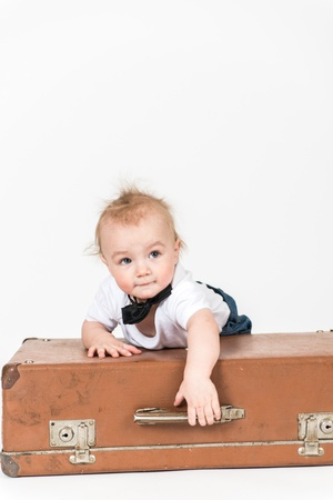 Little boy with the suitcase on the white background photo