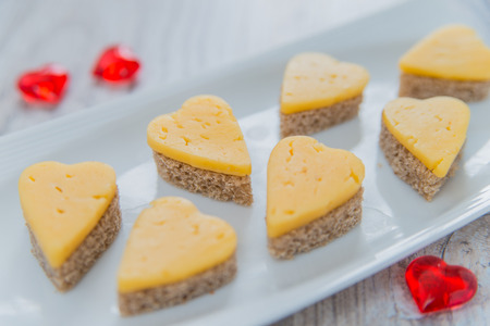 shape: Heart shaped cheese sandwiches on the white plate Stock Photo