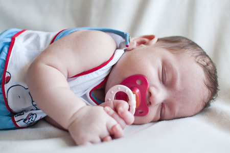 sad little girl: Portrait of the sleeping baby with red nipple Stock Photo