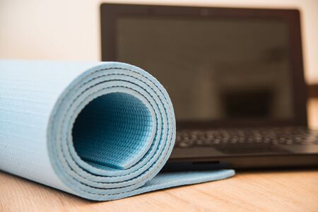 Yoga mat and laptop on the floor. Home fitness during quarantine or for freelancers