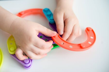 Close up of kid hands playing bright plastic toy constructor. Creative baby make new forms
