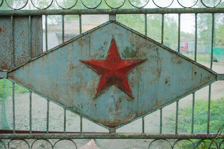 Soviet military five-pointed star on the green scuffed gate. Abandoned restricted zone