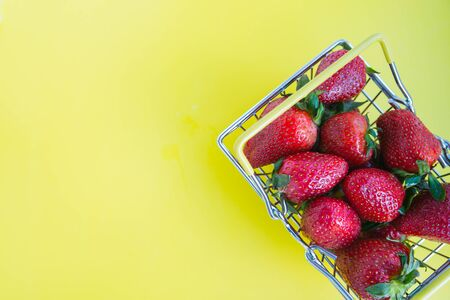fresh strawberries with a shopping basket on a bright yellow background. advertising concept for fresh products. copy space