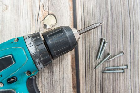 Old screwdriver and screws laying on the wooden background. Top view of the electric screw driver