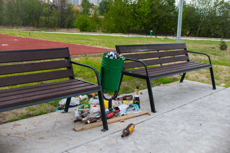 Moscow, Russia - 05/20/2020 - Two benches and a lot of trash near the trash bin. Dirty streets and parks without cleaning Stockfoto - 150300293