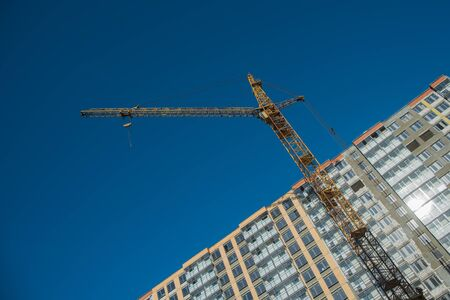Construction crane near new built house. Construction and developing concept