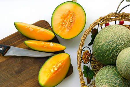 Crop of melons with a green bark and an orange midst. Melons are whole and cut in half.