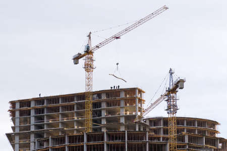 Work of builders and crane in the construction of a multi-storey building.