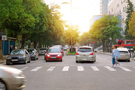 Vida de la ciudad - camino con un paso de peatones, coches y personas.