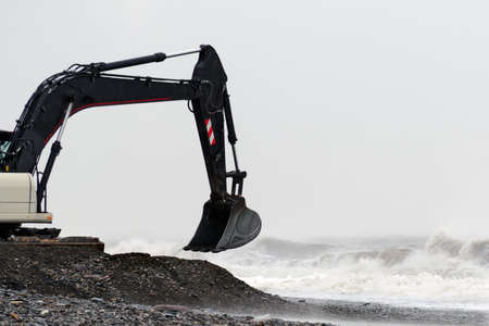 Excavator bucket scoops stones on the seashore in stormy weather. Stock Photo