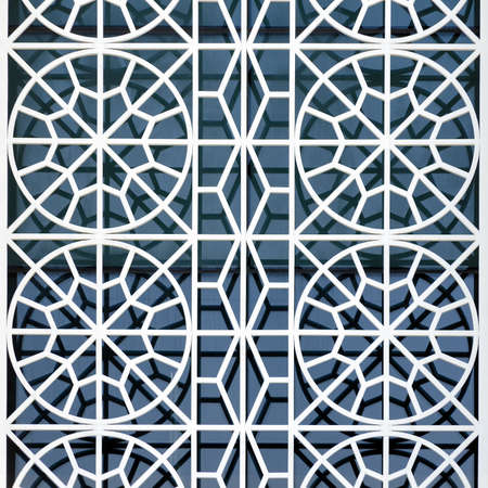 Concept of the architectural design of the exterior of the buildings is a beautiful ornament of the protective grid on the window. Abstract background. Zdjęcie Seryjne