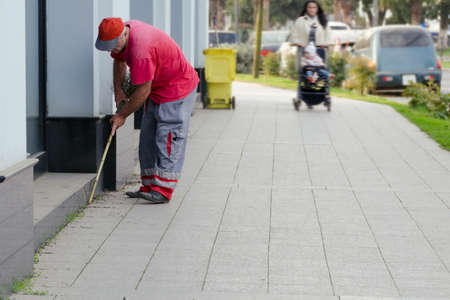 A city cleaner collects garbage near a building near the sidewalk.