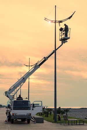 Profession réparation et entretien des lampadaires - voiture avec grue a levé un électricien pour remplacer les ampoules au coucher du soleil en soirée. Filtres toniques. Espace de copie vide pour le texte.
