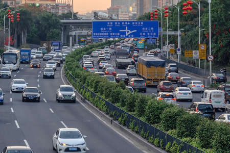 China, Shenzhen, 2018-03-09: Evening traffic in big city, cars on divided highway road, traffic jam at street, busy urban view at sunset. Air pollution in town, benzopyrene, CO2. Photo with blur in motion Редакционное