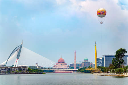 Cyberjaya, Selangor, Malaysia, 02232018: Beautiful city view with lake, Putra Mosque Masjid , bridge, Millennium Monument Alaf Baru, with air balloon from Skyrides Festivals Park Putrajaya. Editorial