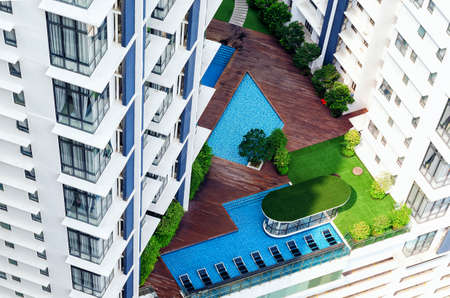 Details of modern building exterior - patio in high-rise building with swimimg pool, lounge zone, green trees. Everything for comfortable stay, ideal exotic vacation.