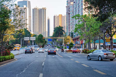 Shenzhen belebte Stadtstraße mit fahrendem Auto, Motorrad, Bürogebäude, Wolkenkratzern. Chinesische Innenstadt.