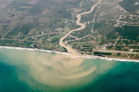 Top view from air, a bird's eye of the river with muddy water, flowing into ocean or sea.