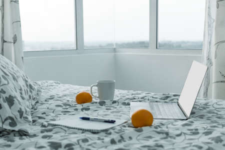 Morning in modern apartment - an open laptop on bed near window, next to cup of coffee, notebook, oranges. Concept of work at home, procrastination, planning. Stock Photo