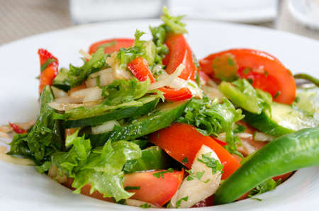 Healthy natural food, fresh salad with vegetables in plate - cucumbers, tomato, greens, close up. Shallow depth of field. Concept of vegetarianism, low calorie diet, weight loss, proper nutrition