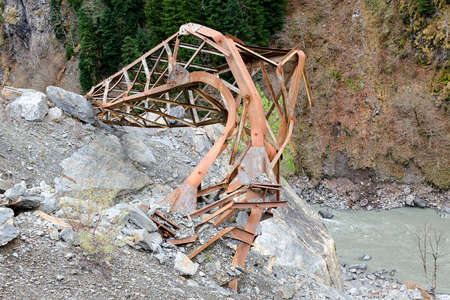 Natural disaster in mountains, implications of rockfalls, force of nature, collapsed electric pole, iron pillar of the collapsed from a mountain slope to the river. Georgia, Svaneti