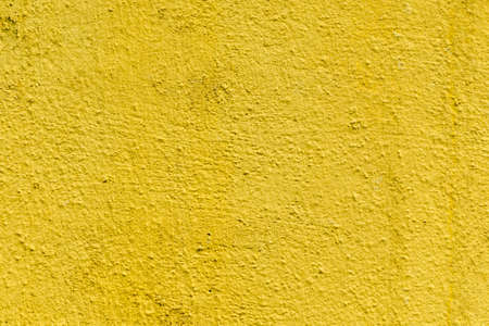 Mustard rough concrete surface, seamless uneven abstract wallpaper. Colour yellow wall, paint on cement texture. Banner backdrop interior design or add text message background.