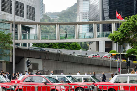 China, Hong Kong downtown, 2018-03-06: Busy city life, crowd of people, road junction, day traffic on the street, a lot of car and taxi on the road, pedestrian bridge with man.