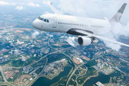 Plane flying sky. Airplane above city. White passenger aircraft climbs through the clouds. Planes and cities.