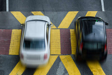 Two cars cross the pedestrian crossing, top view. Photo with motion blur.