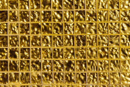 Gold embossed background, square cells. Small golden tile on the wall. Light reflect on surface which is swell texture. Square shape background. Reklamní fotografie