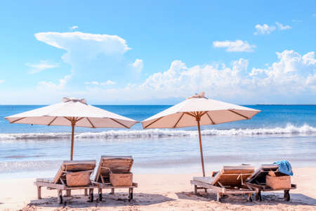Beach with chairs. Sunbeds and umbrella at Bali coast. Luxury beach background. Dreamlike romantic landscape. Concept of an ideal tropic exotic vacation.