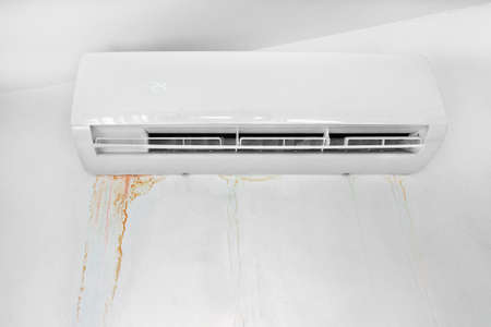 Wall with mold stain due to air conditioner leakage. Mildew stains and destruction of the wall. Improper installation of device.