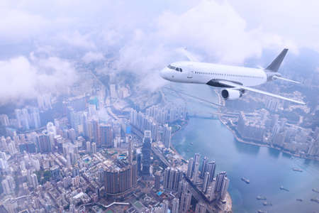 Passenger plane fly to Hong Kong Island. Aerial view at cityscape. Airplane over urban skyline. Concept of travel and air transportation.