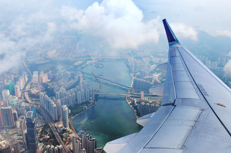 Vliegtuig vliegt over Hong Kong. Passagiersstraalvliegtuig dat boven stedelijke scène vliegt. Hongkong vlucht. Aziatische bestemming. Stockfoto