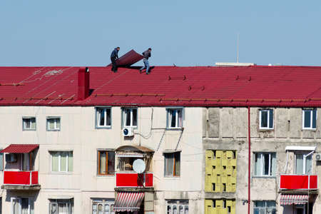 Batumi, Georgia, 2019-03-04: Two men on the roof of a multistorey building do repairs - they change slate. 報道画像