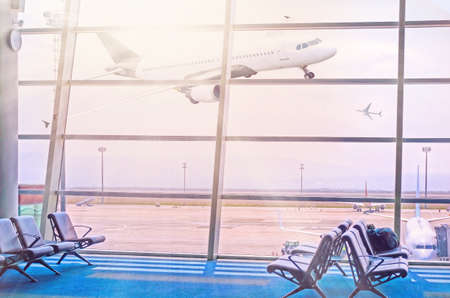 View of the sunlit flying plane through airport window gate. Airport departure lounge seating with a view of the flying plane