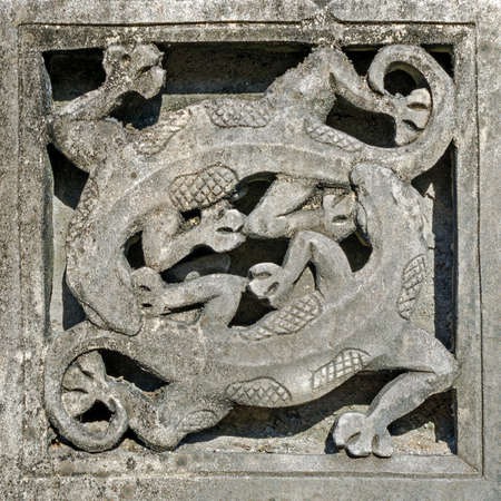 Stone carved sculpture - two lizards, geckos arranged in a circle one after another.  Bali, Indonesia