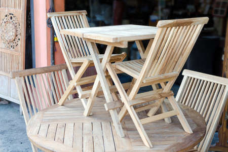 Set of wooden furniture - a table and two chairs. Showroom in a carpenters shop with wood products. Bali, Jimbaran