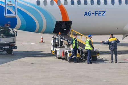 Airport ground staff near the conveyor belt for luggage at the plane. Georgia, Tbilisi, 2019-04-10 Redakční