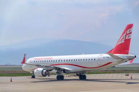 Georgian Airlines plane at the airport on a background of mountains. Georgia, Tbilisi, 2019-04-10