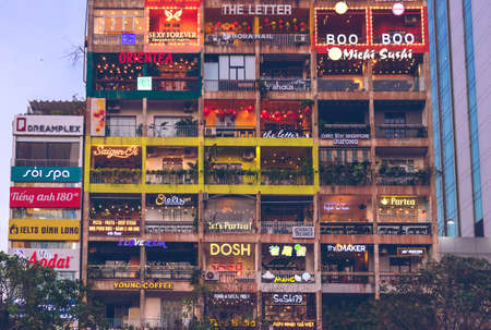 Evening view of the building with balconies in which cafes, shops and bars are located. District 1 Ho Chi Minh, Vietnam: 2019-10-08