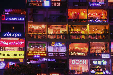 Neon lights from night building.  Night view of the exterior of the entertainment center with lighting in restaurants and shops. 42 Nguyen Hue,  Pedestrian plaza, Ho Chi Minh, Vietnam: 2019-10-08