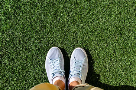 Selfie of shoes standing on the grass. View from above of woman feet in light sneakers on green lawn.  Empty place for text, copy space. Reklamní fotografie