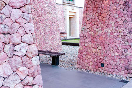 View of the entrance to the building with round walls, covered with pink stone of dry masonry. Bali, Jimbaran