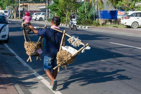 Street food vendor is walking along the road. A man carries snacks - peanuts and quail eggs on the street. Bali, Jimbaran, 2018-04-27 Redakční