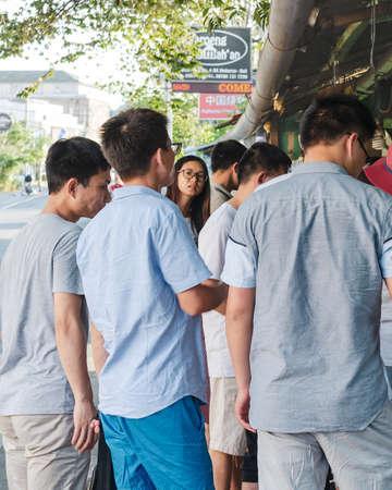 Young asian woman among a group of men on the street. Bali, Jimbaran: 2018-04-27