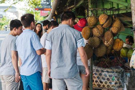 A group of young traveling Asians at a street fruit stall.  Bali, Jimbaran,  2018-04-27